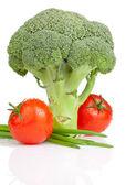 brokolice, dvě rajčata s kapkami a čerstvé jarní cibulkou, izolované na