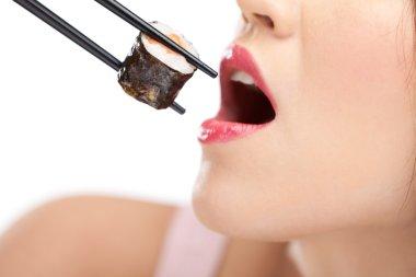 Beautiful girl holding sushi with a chopsticks, closeup