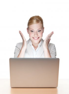 Happy young business woman sitting at a desk with laptop