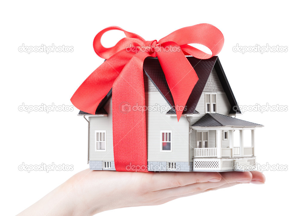 Hand holding house model with red bow