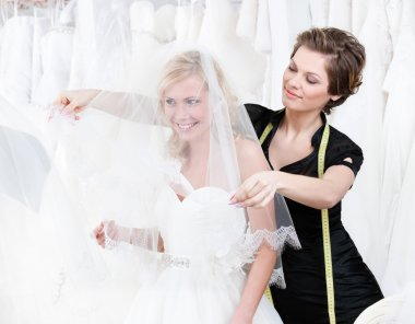 Shop assistant sets the veil of the bride