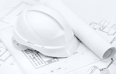 White hard hat on working drawings