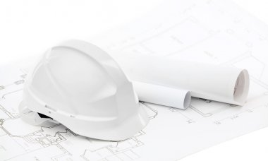 White hard hat near working drawings