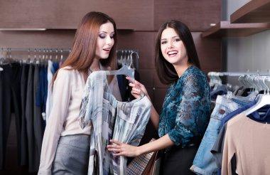 Friends do shopping and discuss a dress