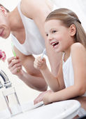 Photo Little girl brushes teeth with her father