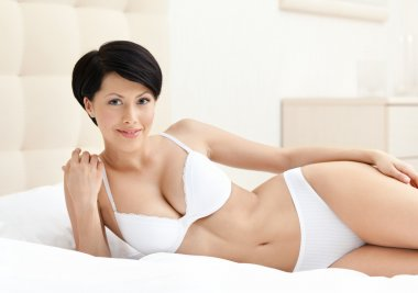 Woman in white underwear is lying in the bed with white bedclothes