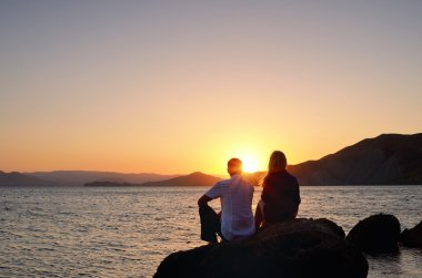 Young girl and boy sitting on a rock and watch the sun