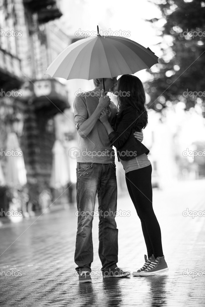Young couple on the street of the city with umbrella