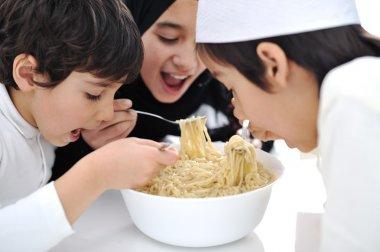 Three Arabic children eating together