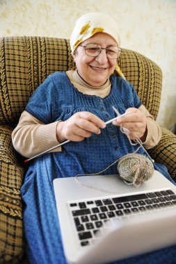 Elderly woman working on laptop in house and knitting