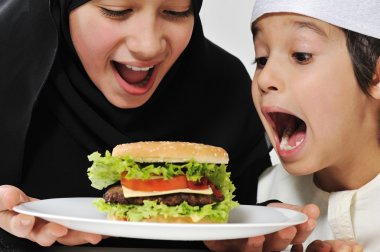 Arabic little male and female eating Burger