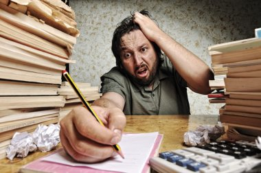 Accountant in problems. Alone working in office with a lot of books around on messy table. Yelling and screaming for bad results.