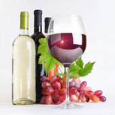 Glass, bottles of wine and grapes