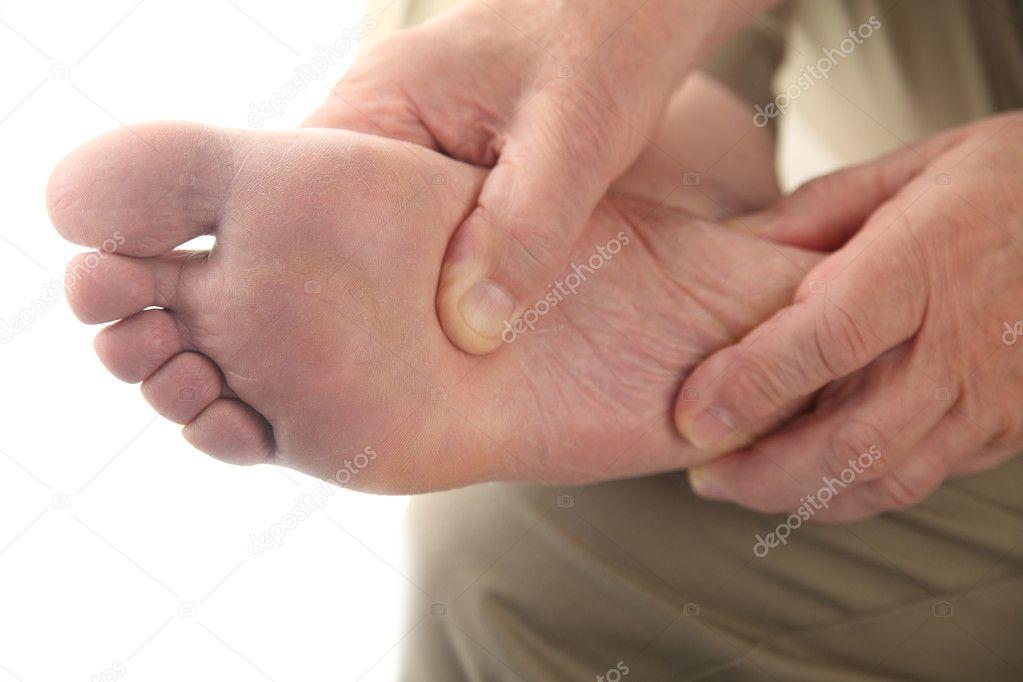 Man checks his aching foot