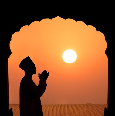 Silhouette of a muslim male praying on the desert