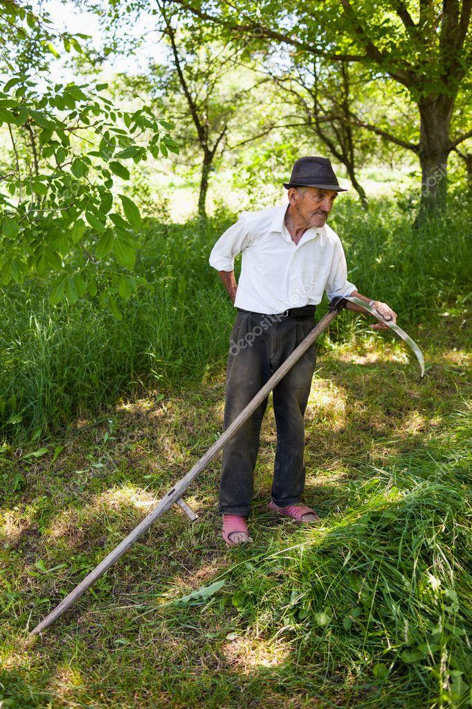 Old man sharpening his scythe