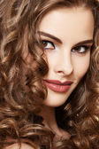 Lovely model with shiny volume curly hair. Pin-up style