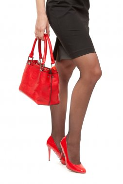 A close-up of a chic red handbag along with sexy female legs wea