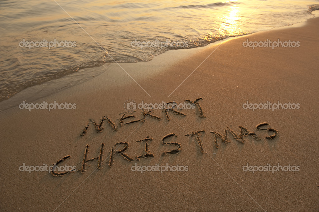 Merry Christmas handwritten in sand on beach
