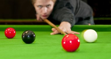 Snooker player placing the cue ball for a shot on black, whilst hitting the red ball (Selective focus and motion blur) stock vector