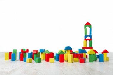 Building blocks toy over floor in white empty interior. Children