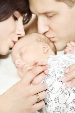 Parents holding newborn baby hand and kissing child. Family and