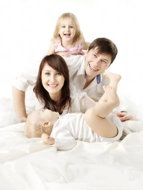 Happy family: parents playing with two kids in bed. Looking at c