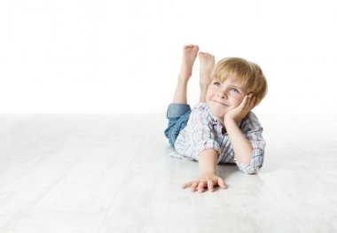 Thinking smiling little boy lying down on floor