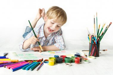 Happy child drawing with brush by multicolor paints