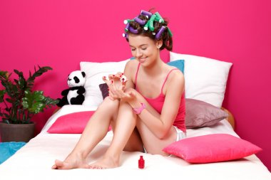 Young nice woman painting her nails with red nail polish