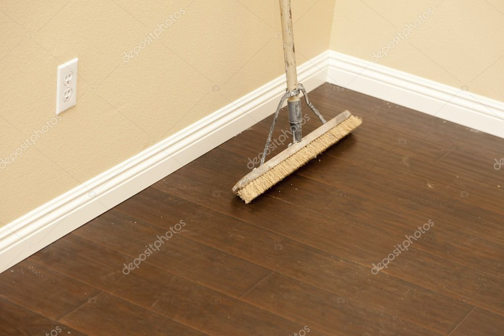 Push Broom On A Newly Installed Laminate Floor And Baseboard Stock