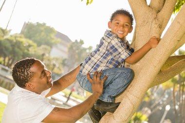 Happy Mixed Race Father Helping Son Climb a Tree