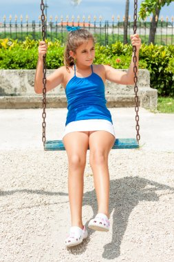 Beautiful hispanic girl riding a swing