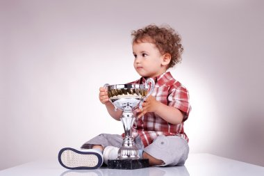 Small boy sitting and holding a trophy