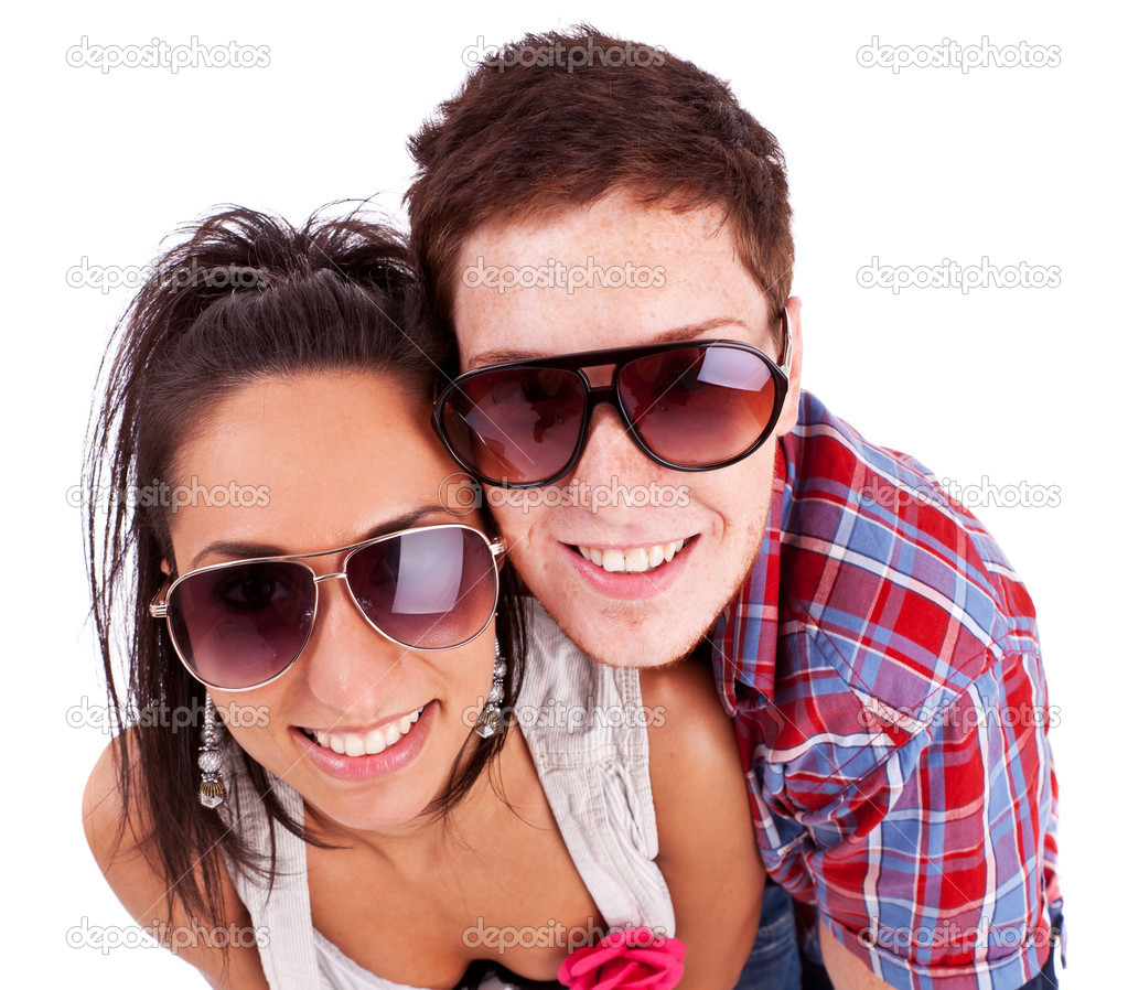 Young Couple Wearing Sunglasses And Smiling At You