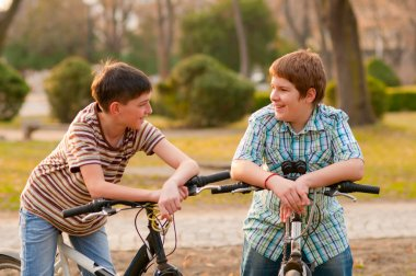 Two happy teenage boys talk in the park while resting on their bicycles