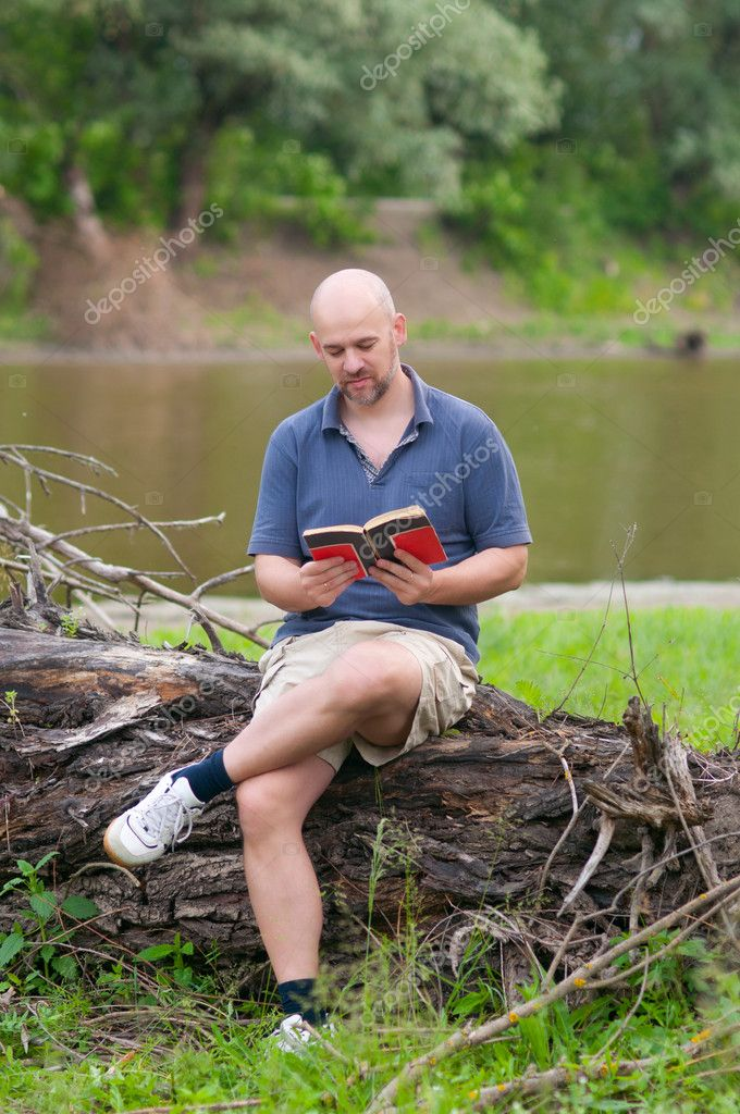 Happy bald man reading the book in the nature