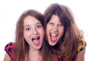 Two beautiful happy teenage girls screaming isolated on white