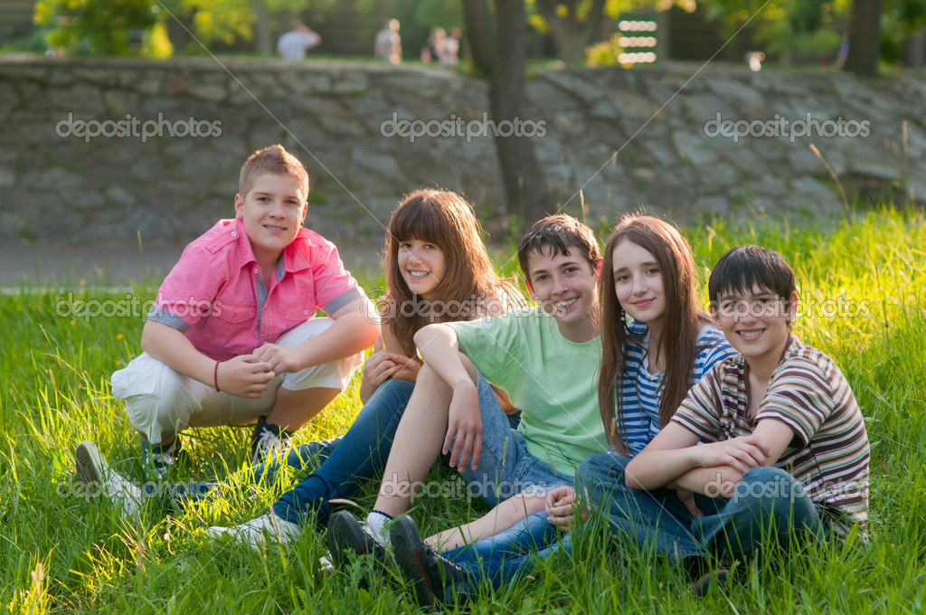 Happy teenage friends spending time together in the park on sunny summer day