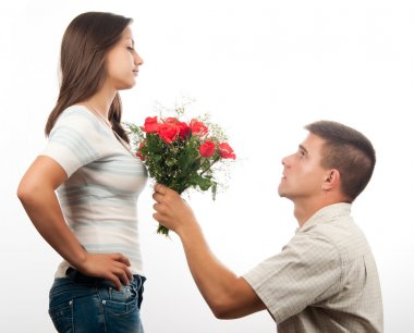 Handsome young man pleading for forgiveness and offering bouquet of roses to his girlfriend