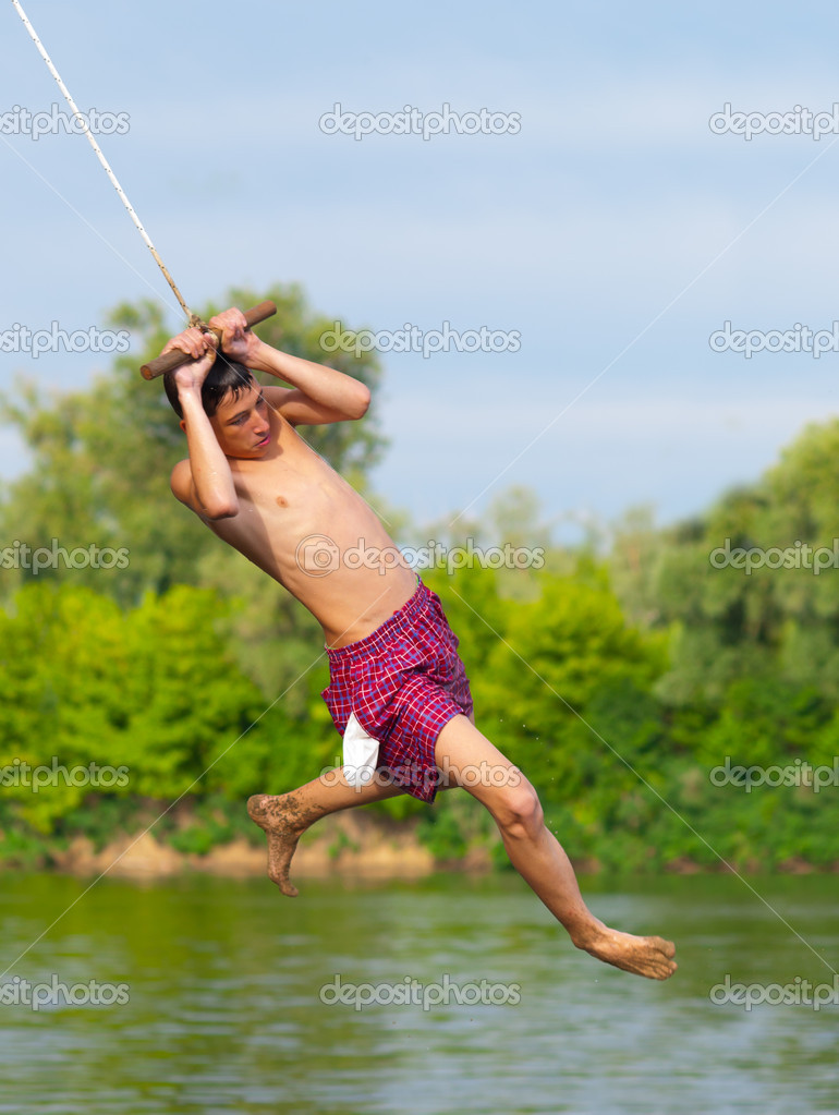 Teenage boy jumping into the river from swinging rope on sunny summer day