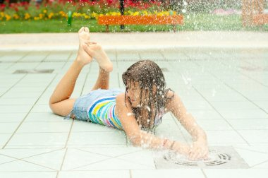 Teenage girl having fun in the water fountain on hot summer day