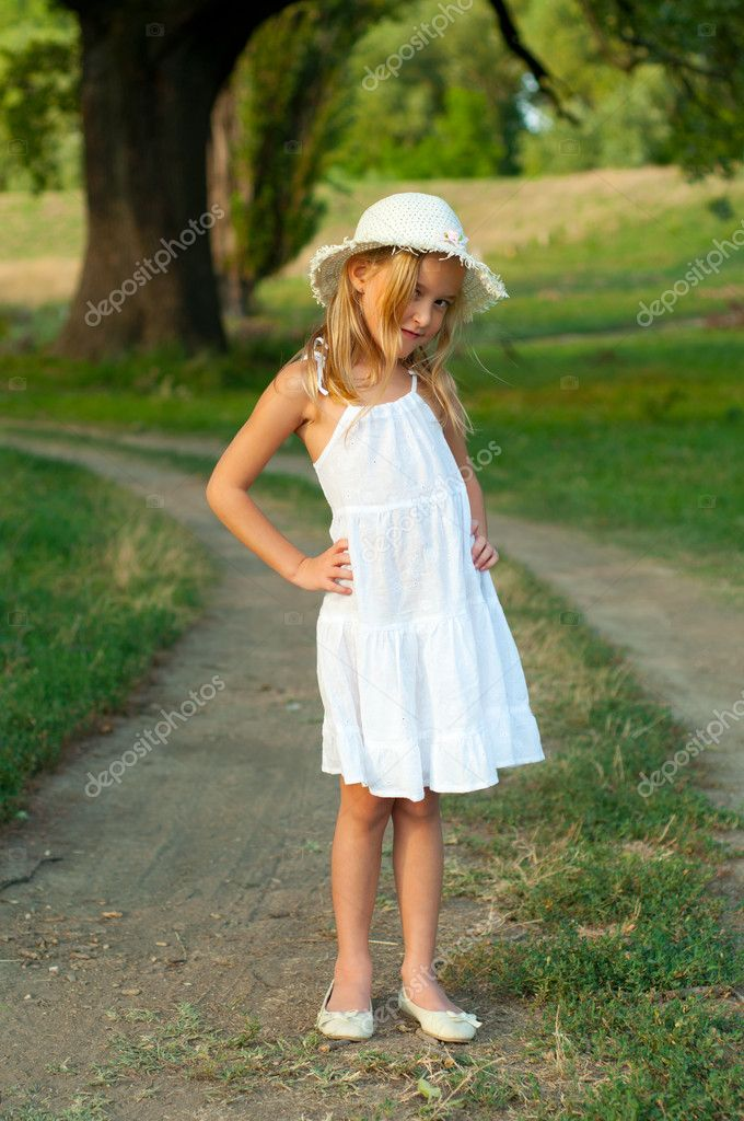 48d53ff6b71c8 Cute little girl in white dress and hat standing on the country road on beautiful  summer day– stock image