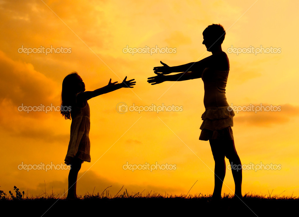 Silhouettes of mother and daughter meeting on the meadow at summer sunset