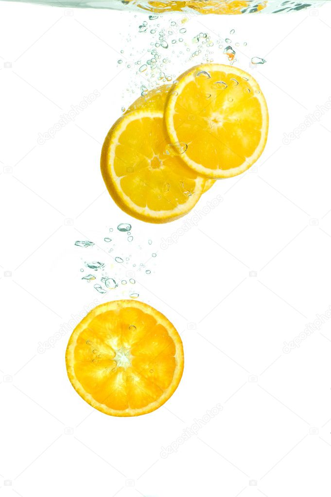 Orange slices falling in water