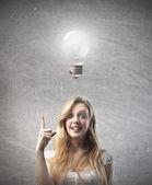 sorridente giovane donna avendo unidea con la lampadina sopra la testa