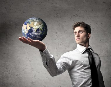 Young businessman holding the Earth in his hand [Elements of this image furnished by NASA]