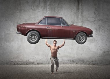 Muscular man holding a car in his hands