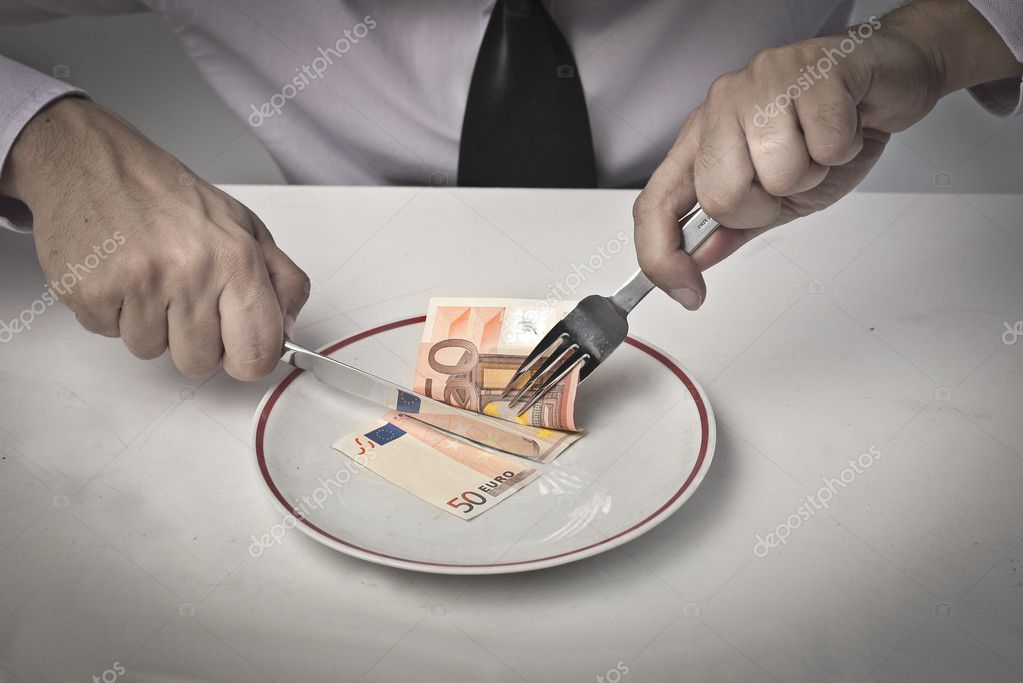 A businessman is cutting a bill for eating it.