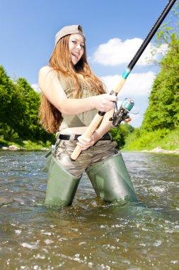 Woman fishing in river, Czech Republic